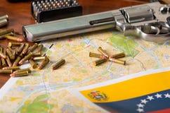 Stäng sig upp av en hagelgevär och en revolver, kassettbälte med kulor med en suddig venezuelansk flagga, på trätabellen Royaltyfria Foton