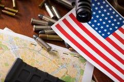 Stäng sig upp av en hagelgevär, och en revolver, kassettbälte med kulor med Förenta staterna sjunker på en översikt, på trätabell Royaltyfri Fotografi