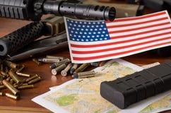 Stäng sig upp av en hagelgevär, och en revolver, kassettbälte med kulor med suddig Förenta staterna sjunker på en översikt, på tr Royaltyfri Foto