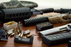 Stäng sig upp av en hagelgevär och en revolver, kassettbälte med kulor, på trätabellen Fotografering för Bildbyråer