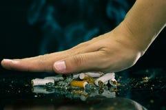 Stäng sig upp av en hand som föreställer röka för STOPP Värld ingen tobakdag Arkivfoto