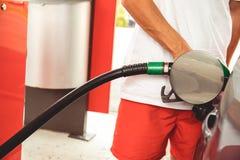 Stäng sig upp av en hand som rymmer en bränsledysa och påfyllning en bil med bensin royaltyfri bild