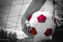 Stäng sig upp av en hand som rymmer en fotbollboll bredvid hans höft Royaltyfria Foton