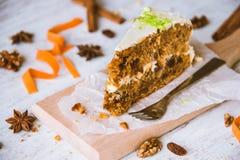 Stäng sig upp av en hemlagad morotkaka med russin, valnötter och kanel över vit träbakgrund Gräddostglasyr på kaka Arkivbild