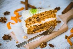 Stäng sig upp av en hemlagad morotkaka med russin, valnötter och kanel över vit träbakgrund Gräddostglasyr på kaka Royaltyfri Bild