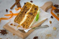 Stäng sig upp av en hemlagad morotkaka med russin, valnötter och kanel över vit träbakgrund Gräddostglasyr på kaka Arkivbilder