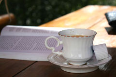 Stäng sig upp av en kaffekopp och en öppnad bok på en tabell Arkivbild