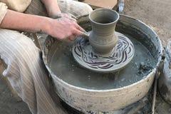 Stäng sig upp av en keramikerförlage som arbetar bak ett krukmakerihjul Krukmakeri modellera av blå lera Gjorde nytt den eleganta royaltyfria bilder