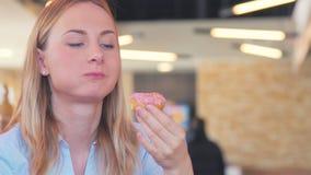 Stäng sig upp av en kvinna som äter munken med färgrik glasyr på kaka och att le stock video