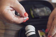 Stäng sig upp av en kvinna som förbereder en glucometerapparat för att testa glukosnivån arkivfoto