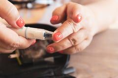 Stäng sig upp av en kvinna som förbereder en glucometerapparat för att testa glukosnivån royaltyfri foto