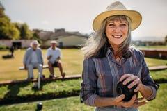 Stäng sig upp av en kvinna som spelar boules i en gräsmatta royaltyfria bilder