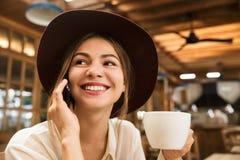 Stäng sig upp av en lycklig älskvärd flicka i hatten som inomhus sitter på kafétabellen, innehavkopp te, arkivfoto
