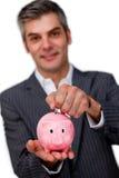 Stäng sig upp av en man som sätter myntet in i en piggy grupp Royaltyfri Foto