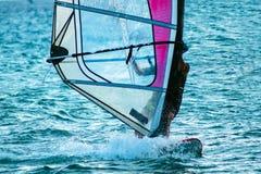 Stäng sig upp av en man som surfar vinden på en ljus sommardag Arkivbilder