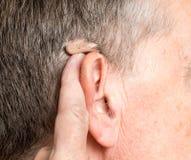 Stäng sig upp av en mycket liten modern hörapparat bak örat royaltyfria bilder