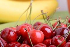 Stäng sig upp av en ny hög av frukt som består av körsbär och bananer arkivbilder