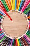 Stäng sig upp av en röd blyertspenna som står ut från en cirkel av många färgrika blyertspennor Arkivbilder