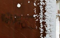 Stäng sig upp av en rostig port under en snöstorm royaltyfria bilder