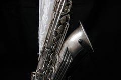 Stäng sig upp av en silversaxofon som dekoreras med en vit torkduk arkivfoton