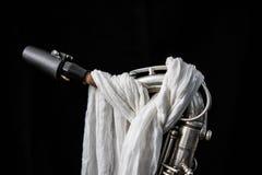Stäng sig upp av en silversaxofon som dekoreras med en vit torkduk royaltyfria bilder