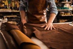 Stäng sig upp av en skomakare som arbetar med lädertextilen royaltyfri fotografi