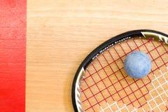 Stäng sig upp av en squashracket och klumpa ihop sig på träbakgrunden royaltyfria foton
