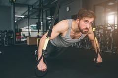 Stäng sig upp av en stark och kraftig man som gör något som sträcker genom att använda trxöglor för det Han gör några liggande ar Arkivfoton