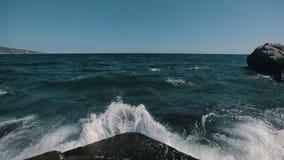 Stäng sig upp av en stor våg som kraschar på stenen och framme besprutar av kameran steadicamskott arkivfilmer