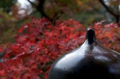 Stäng sig upp av en typisk japansk brostolpe med röda kulöra lönntjänstledigheter i bakgrunden royaltyfria bilder