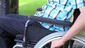 Stäng sig upp av en ung man i en rullstol stock video