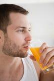 Stäng sig upp av en ung man som dricker orange fruktsaft Fotografering för Bildbyråer