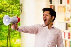 Stäng sig upp av en ung man som ropar med en megafon, med hans arm som sträcks i en suddig bakgrund Royaltyfria Bilder