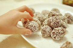 Stäng sig upp av en vit barnhand som upp väljer en handgjord för choklad och söt kakakula för cocos från en platta arkivfoton