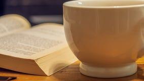 Stäng sig upp av en vit keramisk kaffekopp bredvid boken uppe på en träkaffetabell arkivbild