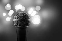 Stäng sig upp av en yrkesmässig mikrofon med suddiga ljus i Arkivfoto