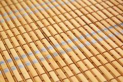 Stäng sig upp av ett bambuunderlägg med den färgrika tråden Royaltyfri Fotografi