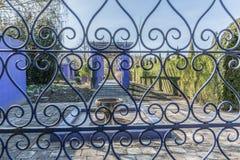 Stäng sig upp av ett fönster med stänger för en metall, och i bakgrunden kan du se en springbrunn en purpurfärgad båge och en grö royaltyfri fotografi