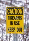 Stäng sig upp av ett gult tecken som läser varningsskjutvapen som är i bruk, håller ut royaltyfria bilder