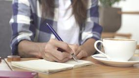 Stäng sig upp av ett kvinnasammanträde och handstil i hennes tidskrift lager videofilmer