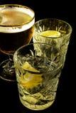 Stäng sig upp av ett vått exponeringsglas av kallt ljust öl med coctailen för skum- och vermutMartini alkohol med gul nolla för c arkivfoton