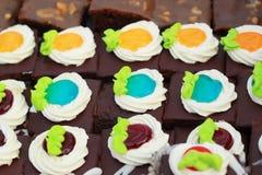 Stäng sig upp av ett val av färgrika donuts. Arkivbilder