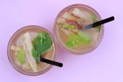 Stäng sig upp av exponeringsglas med hemlagat iste, persikan som smaksättas på en rosa bakgrund Top beskådar royaltyfria bilder