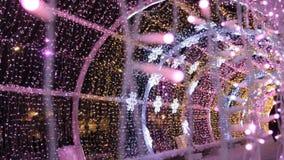 Stäng sig upp av färgade ljusa LEDDE kulor av en girland i ljus tunnel Julgatagarneringar, förberedelse för nytt år i stad lager videofilmer