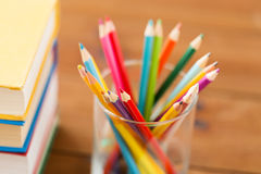 Stäng sig upp av färgpennor eller färga blyertspennor och böcker Arkivbilder