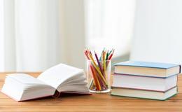 Stäng sig upp av färgpennor eller färga blyertspennor och böcker Royaltyfri Bild