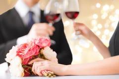 Stäng sig upp av förlovade par som dricker rött vin royaltyfri bild