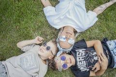 Stäng sig upp av familjen som ligger på grönt gräs ovanför sikt lycklig begreppsfamilj royaltyfria foton