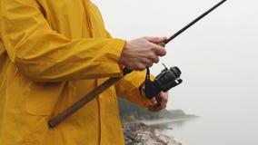 Stäng sig upp av fiskare i gula regnrocksnurranden som rotera fiskerullen i ultrarapid arkivfilmer