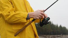 Stäng sig upp av fiskare i gula regnrocksnurranden som rotera fiskerullen i ultrarapid lager videofilmer